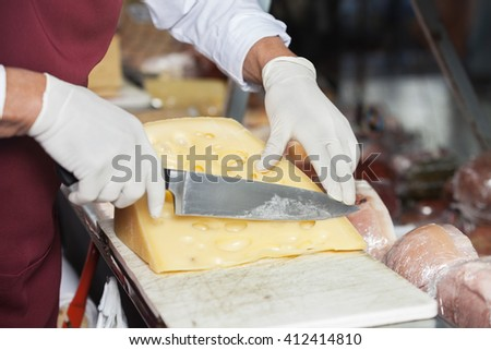 Salesman Slicing Cheese In Shop - stock photo