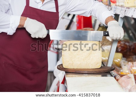 Salesman Slicing Cheese With Double Handled Knife - stock photo