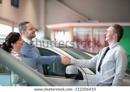 Salesman smiling while shaking the hand of a customer in a car shop - stock photo