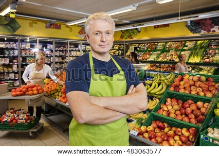 Salesman Standing Arms Crossed By Fruits In Grocery Store