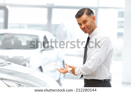 Salesman Standing at the Car Showroom and Showing New Cars - stock photo