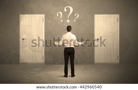 Salesman standing in front of two doors, unable to make the right decision concept with question marks above his head - stock photo