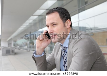 Salesman talking on the phone outside congress center - stock photo
