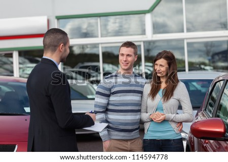Salesman talking to a couple in a dealership - stock photo
