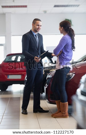Salesman talking to a customer in a car shop - stock photo