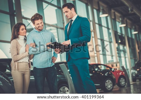 Salesman talking to a young couple at the dealership showroom. - stock photo