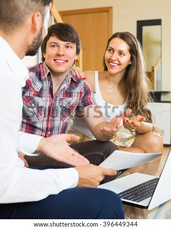 Salesman talking with smiling young man and woman about purchase at home. Selective focus - stock photo