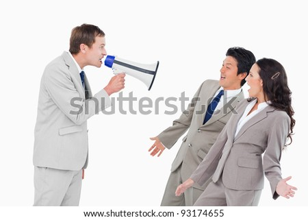 Salesman with megaphone shouting at associates against a white background - stock photo