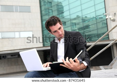 Salesman working outside building of offices - stock photo
