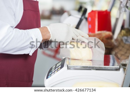 Salesman Wrapping Cheese On Weight Scale - stock photo