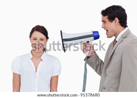 Salesman yelling at colleague with megaphone against a white background - stock photo