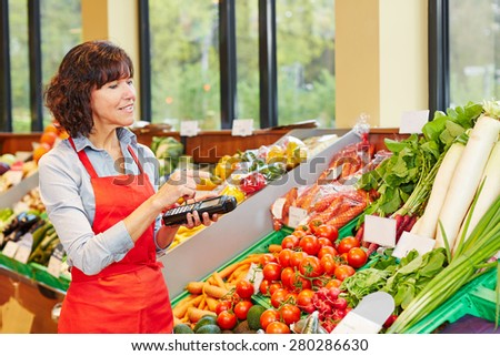Salesperson counting vegetables with mobile data registration terminal for a new delivery in a supermarket - stock photo
