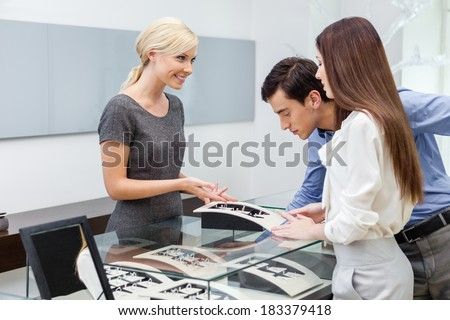 Salesperson helps couple to select jewelry at jeweler's shop. Concept of wealth and luxurious life - stock photo