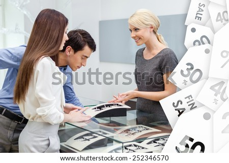 Salesperson helps couple to select jewelry on sale at jeweler's shop. Concept of wealth and luxurious life - stock photo