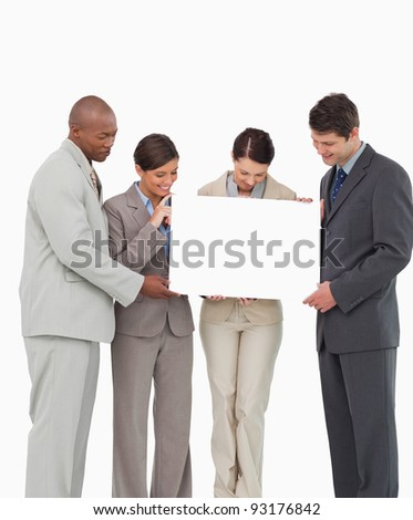 Salesteam holding blank sign together against a white background - stock photo