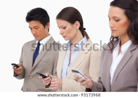 Salesteam looking at their cellphones against a white background - stock photo