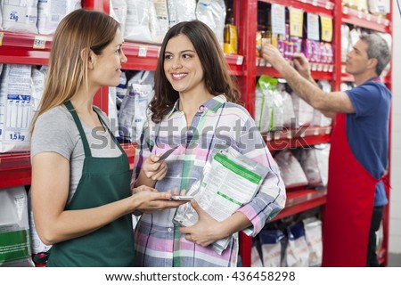 Saleswoman Accepting Payment From Customer In Pet Store - stock photo
