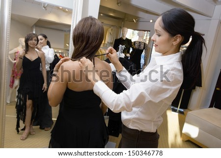 Saleswoman assisting female customer with dress in store - stock photo