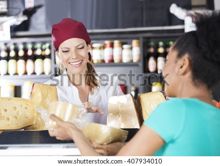 Saleswoman Assisting Young Customer In Buying Cheese - stock photo