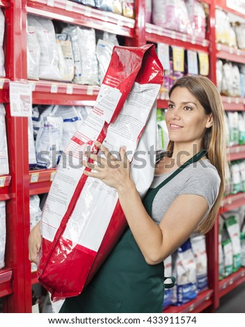 Saleswoman Carrying Food Package In Pet Store - stock photo
