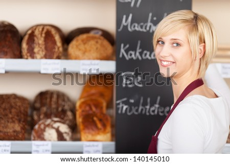 saleswoman in bakery writing offers on blackboard - stock photo