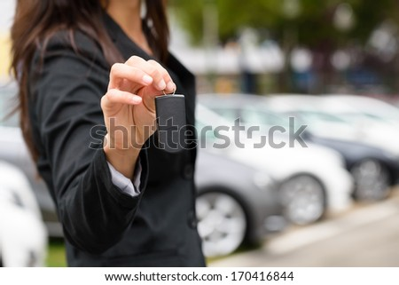 Saleswoman offering car key. Transport sales and rental concept.