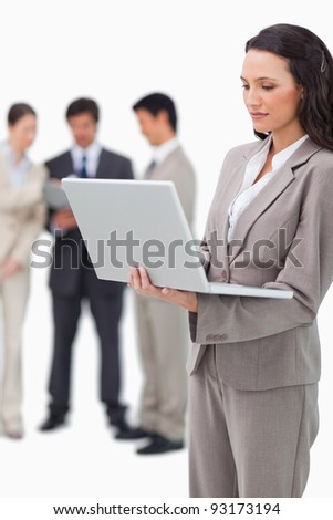 Saleswoman standing with laptop and colleagues behind her against a white background