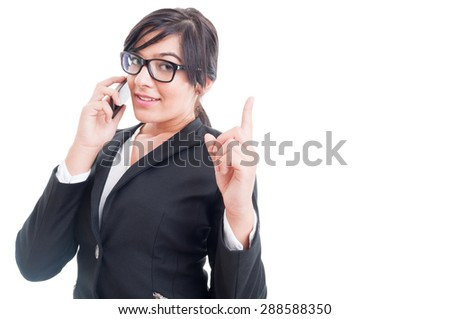 Saleswoman talking on the phone and making wait gesture with finger up