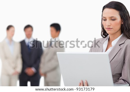 Saleswoman with laptop and colleagues behind her against a white background