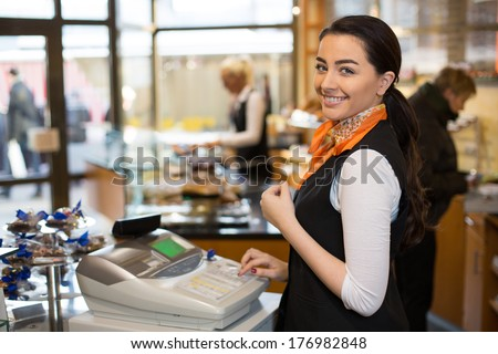 Saleswoman working at cash register in shop - stock photo
