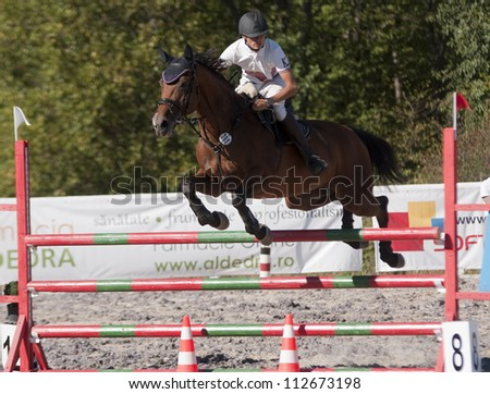 SALICEA, ROMANIA - SEPTEMBER 9: An unidentified competitor jumps with his horse at the Napoca Cup Sport Horse, September 9, 2012 in Salicea, Romania - stock photo