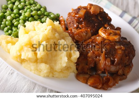 Salisbury steak with mashed potatoes and green peas close-up on a plate on the table. horizontal