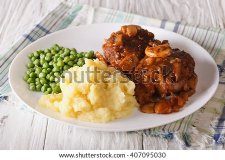 Salisbury steak with potatoes and green peas close-up on a plate on the table. horizontal
