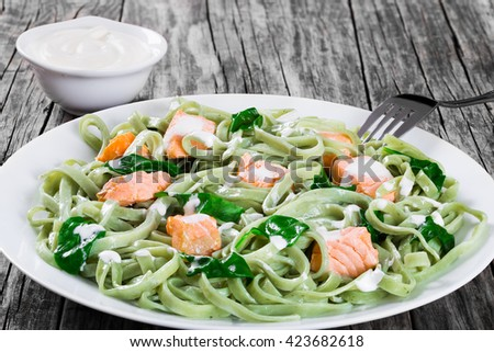 salmon and spinach fettuccine alfredo pasta on white dish, cream sauce in a gravy boat on dark wooden table, italian style, side view, close-up - stock photo