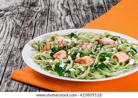 salmon and spinach fettuccine pasta on white dishes and orange table napkin on a rustic italian style, top view  - stock photo