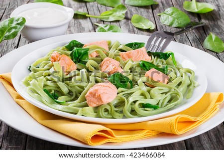salmon and spinach fettuccine pasta on white dishes and table napkin, cream sauce in a gravy boat on dark wooden italian style, side view  - stock photo