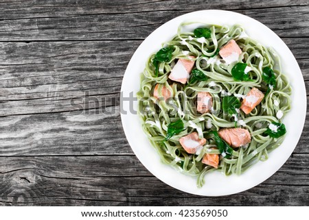 salmon and spinach fettuccine pasta on white dishes, italian style, top view  - stock photo