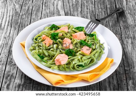 salmon and spinach fettuccine pasta on white dishes with fork and napkin on a table, italian style, close-up  - stock photo
