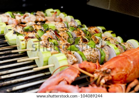 Salmon and Vegetable Skewers and Lobster are on the barbecue.