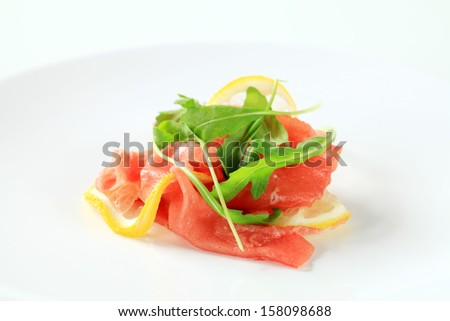 Salmon appetizer with fresh arugula and lemon