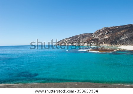 Salmon Beach Bay in Torndirrup National Park near Albany, Western Australia, burnt vegetation on cliff coast, turquoise Southern Ocean, blue sky as copy space. - stock photo