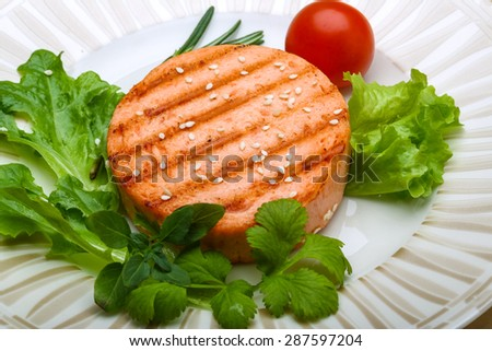Salmon burger cutlet with sesame seeds and salad - stock photo