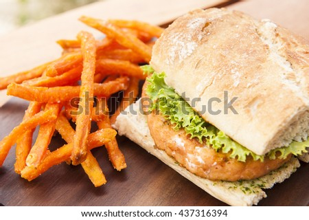 Salmon burger with lettuce and pesto sauce  served with sweet potato fries