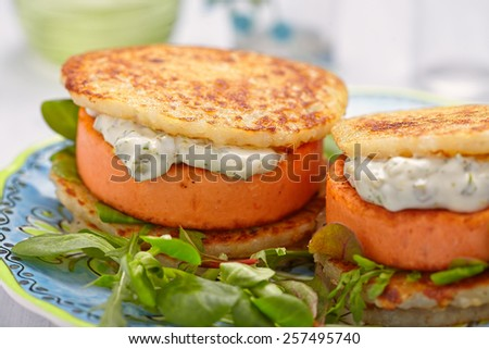 Salmon burger with potato pancakes and tartar sauce - stock photo