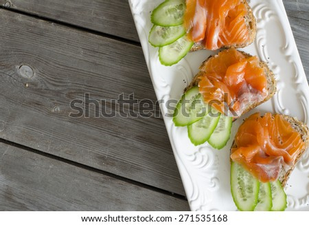 Salmon Canapes. Small sandwiches with salmon and cucumber. - stock photo