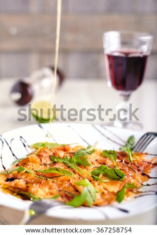 Salmon carpaccio close up with arugula leaves on it, fork near it, and jet of olive oil, that fill the carpaccio on neutral wooden background - stock photo