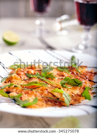 Salmon carpaccio close up with arugula leaves on it, fork near it,  on neutral wooden background - stock photo