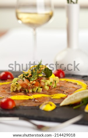 Salmon Carpaccio on Black Dish with White Wine