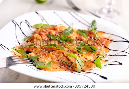 Salmon carpaccio on white plate with balsamic vinegar  - stock photo
