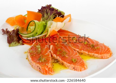 Salmon carpaccio with chopped vegetables in a restaurant  - stock photo